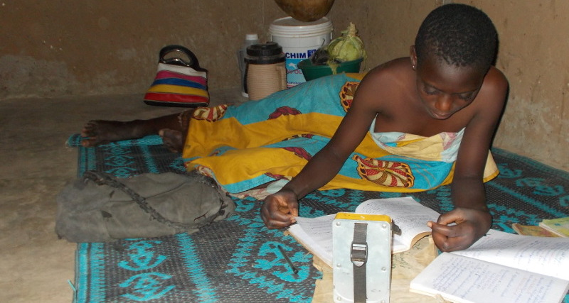 Schoolgirls revising her lessons in the light of the solar lamp offered as part of the sponsorship